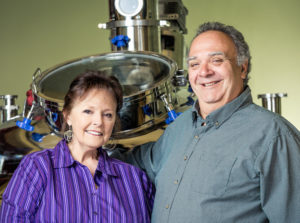 Portrait of Ally and Mike Benbrook standing in front of the distillery machine