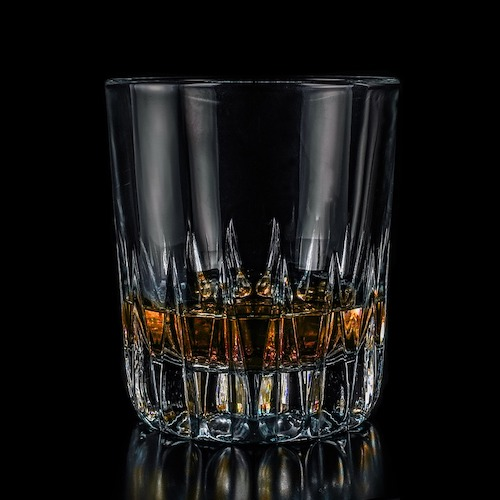 Glass of Whiskey against black background
